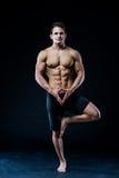 Den unga starka idrottsman nen gör yoga på svart bakgrund Arkivbilder
