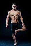 Den unga starka idrottsman nen gör yoga på svart bakgrund Royaltyfri Foto
