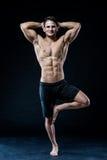 Den unga starka idrottsman nen gör yoga på svart bakgrund Arkivfoton