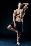 Den unga starka idrottsman nen gör yoga på svart bakgrund Royaltyfri Fotografi