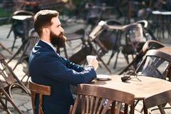 Den unga stilfulla affärsmannen dricker kaffe i morgonkafét royaltyfria bilder