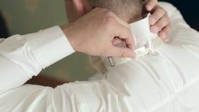 Den unga stilfulla brudgummen sätter flugan på skjortan lager videofilmer