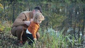 Den unga stilfulla familjen som sitter i gräset på leken för flodbanken, farsa- och sonoch, har roligt stock video