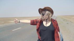 Den unga stilfulla flickan i cowboy beklär att göra hake-att fotvandra i öken, på vägen Hon bär ryggsäcken och hatten passerande lager videofilmer