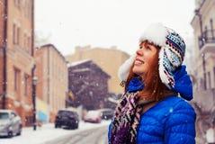 Den unga stilfulla flickan jublar första snö Insnöat staden låt snow Ung flickalås snön med hans händer Arkivbilder