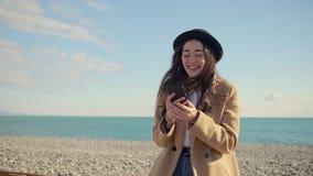 Den unga stilfulla flickan pratar i socialt förtjänar i smartphone på havstranden lager videofilmer