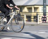 Den unga stilfulla kvinnacyklisten i svart kläder korsar vägen med cykeln, medan köra till och med övergångsställe på en tvärgata arkivbilder