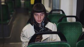 Den unga stilfulla kvinnan som bär på hörlurar och lyssnar till musik på mobiltelefonen transporterar offentligt stadslampor arkivfilmer