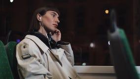 Den unga stilfulla kvinnan som bär på trådlös hörlurar och lyssnar till musik på mobiltelefonen transporterar offentligt Stad stock video