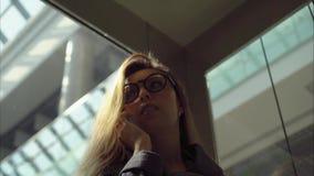 Den unga stilfulla kvinnan talar i hissen vid telefonen stock video