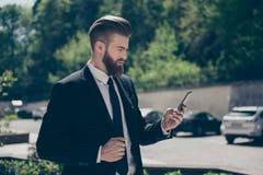 Den unga stilfulla skäggiga affärsmannen i en flott dräkt bläddrar royaltyfri fotografi