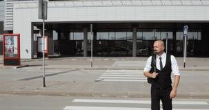 Den unga stilfulla skalliga affärsmannen kommer ut från affärsmitten, flygplatsen, kontor Begrepp: en ny affär, resa lager videofilmer
