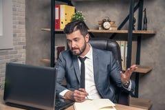 Den unga stilfulla stiliga affärsmannen läser post i hans varvöverkant som förvånas från nyheterna som han har fått Lite besviket royaltyfri fotografi
