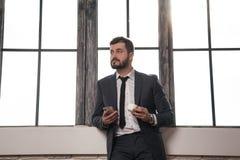 Den unga stilfulla stiliga affärsmannen står vid fönstret på hans kontor som har ett kaffeavbrott och rymmer en mobiltelefon i ha royaltyfri bild