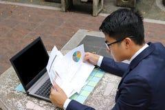 Den unga stiliga affärsmannen analyserar finansiella diagram, och dokument mot bärbara datorn i den offentliga det fria parkerar royaltyfri fotografi