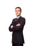 Den unga stiliga affärsmannen i svart dräkt är den stående raksträckan med korsade armar, den fulla längdståenden som isoleras på arkivbilder