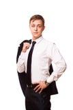 Den unga stiliga affärsmannen rymmer ett omslag i hans en hand och den annan handen i hans fack stående som isoleras på royaltyfri foto