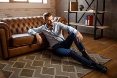 Den unga stiliga affärsmannen sitter på golv och poserar i hans eget kontor Han ser rak med förtroende sexigt barn för man royaltyfri fotografi