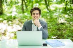 Den unga stiliga affärsmannen som arbetar på bärbara datorn på kontorstabellen med händer på hakaleende på kameran i gräsplan, pa Arkivbild