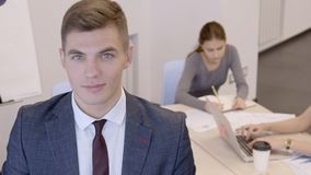 Den unga stiliga affärsmannen står i kontoret med hans kvinnliga kollegor och le stock video