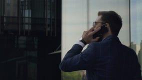 Den unga stiliga affärsmannen talar på telefonen som promenerar den New York gatan lager videofilmer