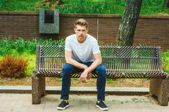 Den unga stiliga amerikanska mannen som kopplar av på gatan, parkerar i New York Royaltyfria Bilder