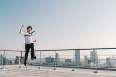 Den unga stiliga asiatiska affärsmanbanhoppningen firar att segra för framgång poserar på byggnadstaket Arbete, jobb eller framgå royaltyfri fotografi