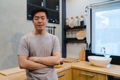 Den unga stiliga asiatiska mannen förbereder salladmat och matlagning i köket Royaltyfri Bild