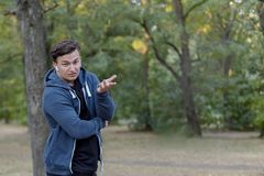 Den unga stiliga caucasian mannen med förvirrat framsidauttryck och den skeptiska gesten på gräsplan parkerar, att bära som är ti arkivbilder