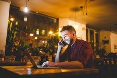 Den unga stiliga Caucasian mannen med skägget och toothy leende i röd skjorta arbetar bak bärbara datorn, händer på tangentbordsa royaltyfria bilder