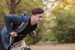 Den unga stiliga caucasian mannen som cyklar på, parkerar royaltyfri bild