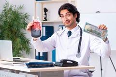 Den unga stiliga doktorn i blodtransfusionbegrepp arkivfoton