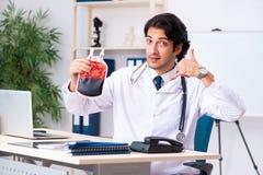 Den unga stiliga doktorn i blodtransfusionbegrepp arkivbild