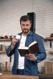 Den unga stiliga grabben har hans morgonkaffe på köket och läser en bok arkivfoton