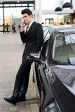 Den unga stiliga manen, modellerar av danar, med lyxiga bilar Royaltyfria Foton