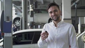 Den unga stiliga mannen i bilservice shoppar visa hans biltangenter och le på bakgrunden av hans bil lager videofilmer