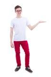 Den unga stiliga mannen i det vita t-skjortan innehavet något i hand är Arkivbild