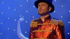 Den unga stiliga mannen i rött svans-lag sjunger på etappen i teater lager videofilmer