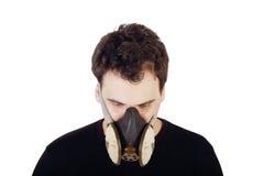 Den unga stiliga mannen i svart skjorta och respirator ser ner Arkivbilder