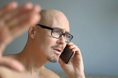 Den unga stiliga mannen i svarta exponeringsglas talar på telefonen Stora problem, skandal, dåliga nyheter closeup isolerad manst arkivfoto