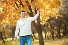 Den unga stiliga mannen i tröja och jeans som blir i höstapelsin, parkerar att le och att vinka till någon arkivbild