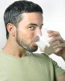 Den unga stiliga mannen med att dricka för skägg mjölkar Arkivfoton