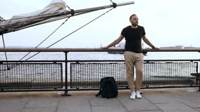 Den unga stiliga mannen med ryggsäckanseende på pir nära bogspröt, det motoriska fartyget är kommande till kusten stock video