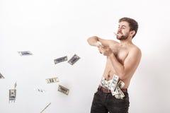 Den unga stiliga mannen med skägget som rymmer många hundra dollarräkningar och, kastar dem in i luften Pengar och rikedom Royaltyfri Fotografi