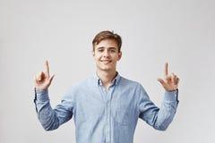 Den unga stiliga mannen ser upp och att peka hans fingrar som hoppas att alla nummer i hans lottsedel ska matcha och royaltyfria bilder