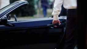 Den unga stiliga mannen sitter i bilen Den manliga affärsmannen sitter i en cabriolet lager videofilmer