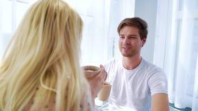 Den unga stiliga mannen sitter på golv och drinkmorgonkaffe med den blonda kvinnan lager videofilmer