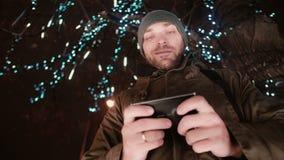 Den unga stiliga mannen som använder smartphonen på anseendet för julnatten under ett träd, dekorerade med mousserande ljus arkivbild