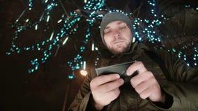 Den unga stiliga mannen som använder smartphonen på anseendet för julnatten under ett träd, dekorerade med mousserande ljus stock video