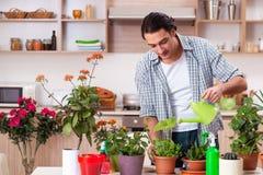 Den unga stiliga mannen som hemma odlar blommor arkivfoto